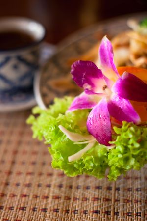 Beautifully served thai noodles with orchid and a cup of tea, shallow DOF, focus on the flower photo