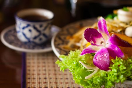 Beautifully served thai noodles with orchid and a cup of tea, shallow DOF, focus on the flower Stock Photo - 4586439
