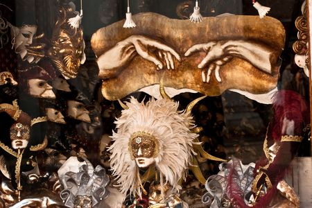 Venice shop window: masks and a copy of the detail of The Creation of Adam by Michelangelo (hands) photo