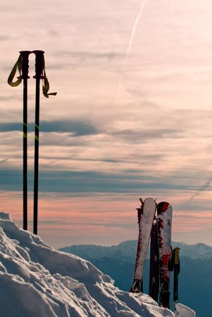 Skiing equipment over the high mountain landscape at sunset