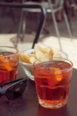 At the bar: two glasses with long drinks with oranges and potato chips on the table