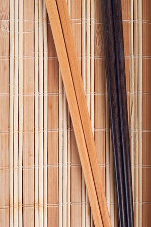 A pair of chopsticks on bamboo mat photo