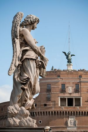 One of Bernini`s statue of angels (Angel with garment and dice) on Ponte Sant`Angelo, in front of Castel Sant`Angelo in Rome  photo