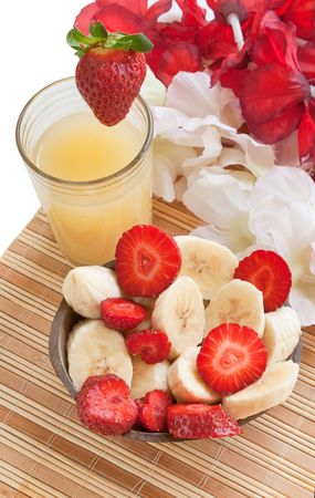 Colorful fruits (cut bananas and strawberries served in a coconut, with a glass of juice) photo