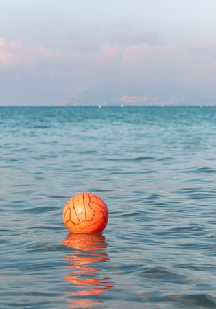 Orange waterpolo ball floating in the sea waters photo