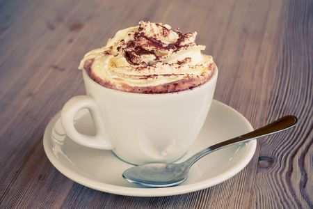 hot chocolate drink: A cup of hot chocolate with cream on a wooden textured table