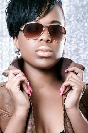 Beautiful girl wearing a leather jacket, studio portrait on shiny background