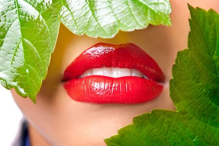 Closeup of a womans face covered with green leaves, focus on red lips photo