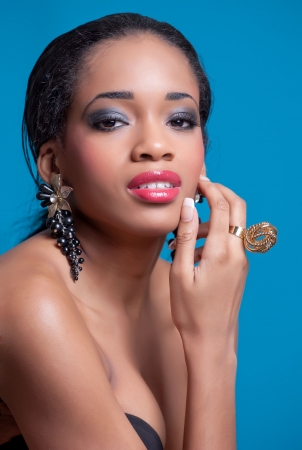 A beauty shot of a pretty black woman wearing fashionable jewelry, isolated on blue Stock Photo - 7343338