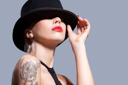 face covered: Sexy girl wearing a black hat, isolated on grey