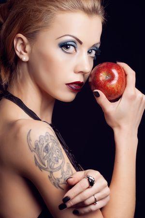 Sensual blond girl offering an apple