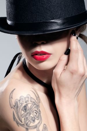 labbra sensuali: Colpo di bellezza di una ragazza sexy che indossa un cappello nero, isolato su grigio