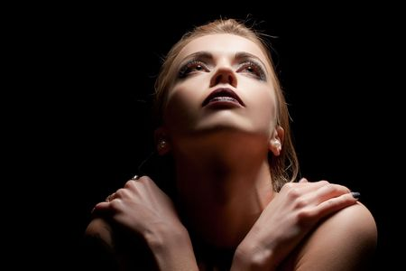 20s  closeup: Young sensual woman in darkness looking up at light Stock Photo