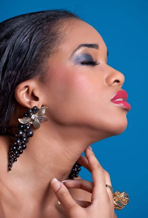 Portrait of a young sensual woman with closed eyes touching her neck, isolated on blue Stock Photo - 7563905
