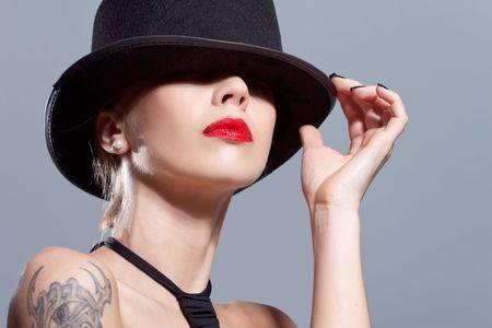 회색에 고립 된 검은 모자를 쓰고 섹시한 여자 스톡 콘텐츠
