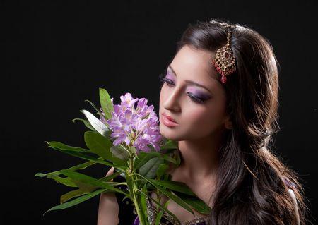 Beautiful asian bride holding purple flowers, isolated on black