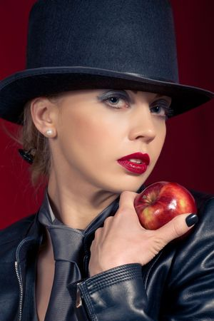Sensual blond girl wearing a hat, offering an apple  photo