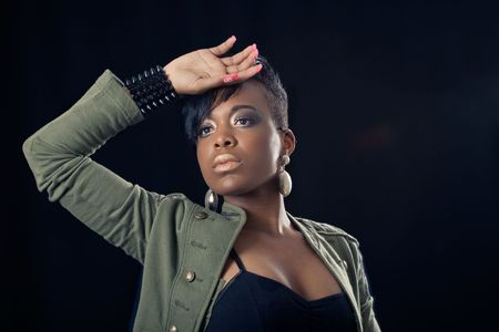 Portrait of african american woman, looking away and protecting her face with her hand against light, isolated over black photo