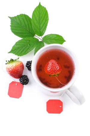 White cup of fruit tea with strawberries as teabags, isolated on white photo