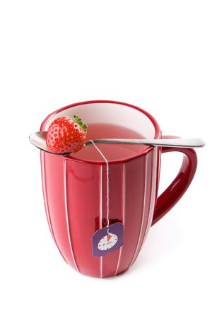 Big cup of fruit tea with strawberries as teabags, isolated on white photo