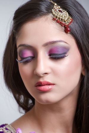 Closeup portrait of a beautiful indian bride with purple makeup  Stock Photo