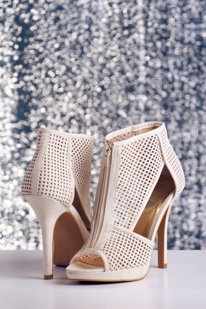 Pair of womens high heel shoes on shiny background