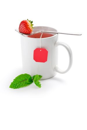 White cup of fruit tea with strawberry as teabag, isolated on white photo