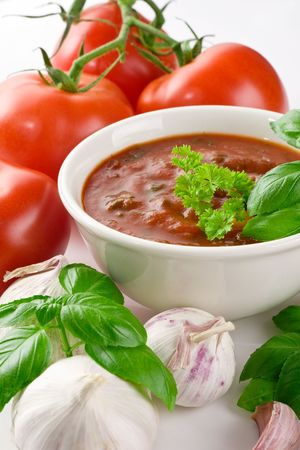 Close-up shot of tomato soup in bowl, set with garlic, tomatoes and basil Stock Photo