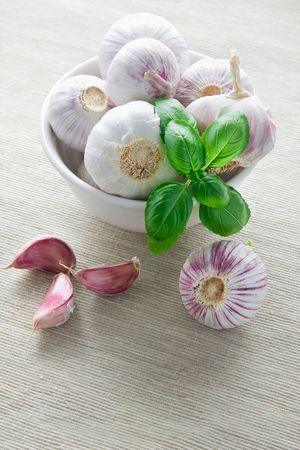 Cloves of garlic in bowl and leaves of fresh basil photo