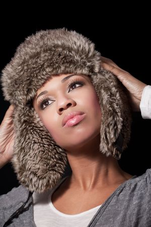 Winter fashion: beautiful happy young woman wearing fur hat, isolated on black  photo
