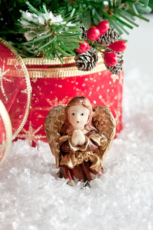 Christmas decorations: praying angel figurine in snow under the tree Stock Photo - 8265636