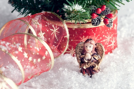 Christmas decoration - praying angel with golden wings in snow photo