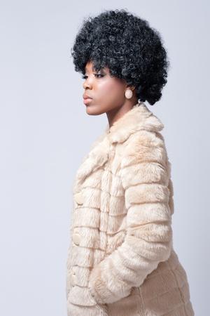 Young beautiful black woman wearing a fur coat Stock Photo - 8592431