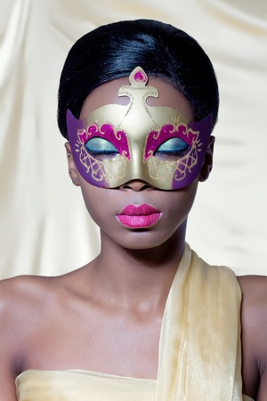 Beautiful young woman wearing a golden carnival mask, isolated on golden photo