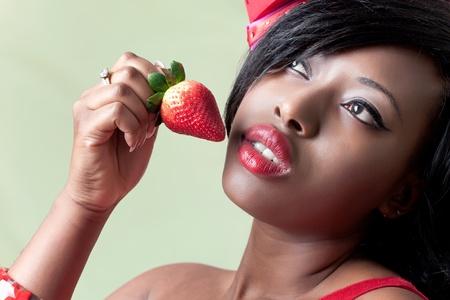 Beautiful young black woman eating a strawberry, closeup shot photo