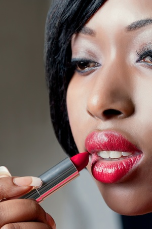 Closeup shot of beautiful woman applying red lipstick photo