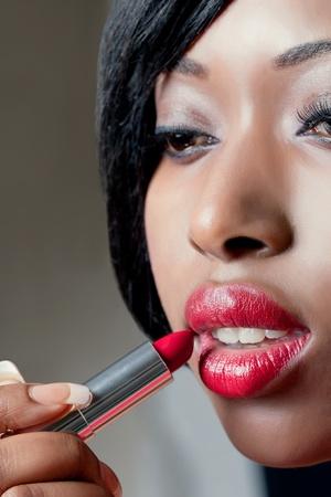 Closeup shot of beautiful woman applying red lipstick Stock Photo - 8849270
