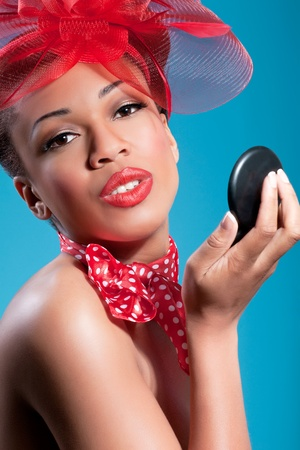 Beautiful smiling pinup girl holding a mirror and checking makeup Stock Photo - 8853281