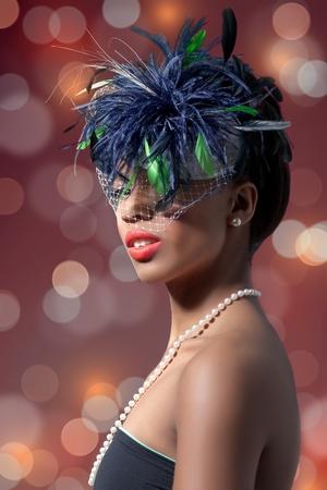 Beautiful fashion model wearing a veil hat on blur background photo