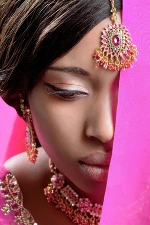 Beautiful indian woman wearing golden jewelry, closeup shot