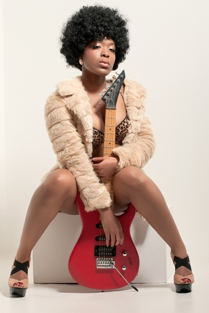 Young beautiful woman wearing fashionable clothes holding a guitar, studio portrait photo