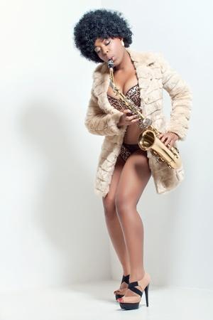 색소폰, 복고 스타일 스튜디오 초상화를 연주하는 아름 다운 정력적 인 여자