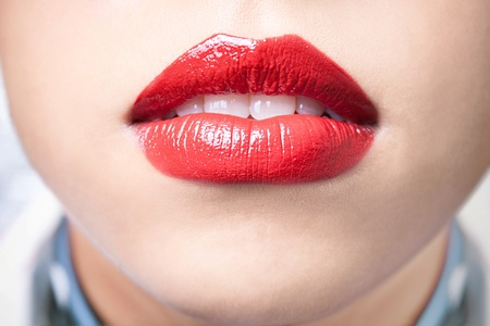 Close-up shot of female lips with bright red lipstick photo