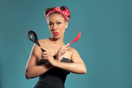 Beautiful happy pin-up style housewife with kitchen utensils, retro style studio portrait photo