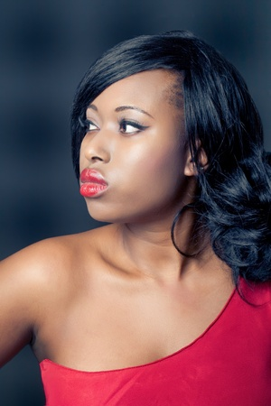 Beautiful young black woman wearing a red dress, profile shot, isolated on black photo