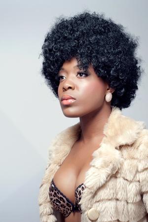 Young beautiful black woman wearing a fur coat photo