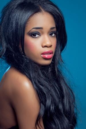 cabello rizado: Sensual joven y bella mujer con cabello rizado largo y maquillaje de moda oscura, aislados en azul