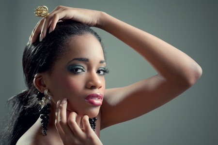Young beautiful sensual black woman with fashionable golden jewelry photo