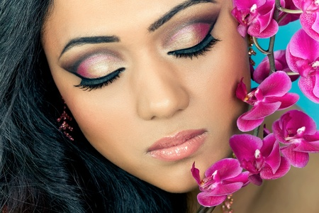Closeup shot of a beautiful young woman's face with purple orchid flowers