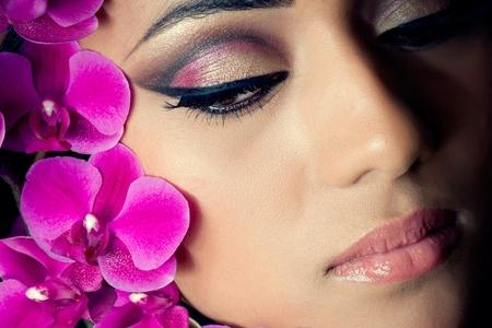 보라색 난초 꽃으로 아름 다운 젊은 여자의 얼굴의 근접 촬영 총